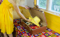 Woman with yellow dress put hat old suitcase Royalty Free Stock Photo