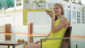 Woman in yellow dress sitting in chair near swimming pool. Using her smartphone, talking with friend. Smiling happy woman in yellow dress sitting in chair near stock video footage