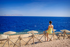 Woman in a yellow dress sitting on a fence on the beach and looking at sea Royalty Free Stock Image