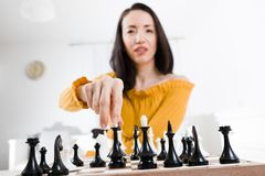 Woman in yellow dress sitting in front of chess - going to win royalty free stock images