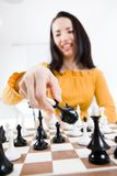 Woman in yellow dress sitting in front of chess - put into checkmate royalty free stock images