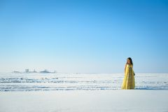 Woman in yellow dress on the snow field Stock Photo