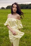 Woman in yellow dress stands in a field Royalty Free Stock Photo