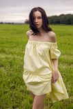 Woman in yellow dress stands in a field Stock Photography