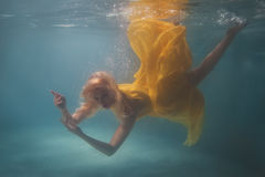 Woman in yellow dress under water. Royalty Free Stock Photography