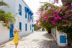 A woman in yellow dress walking in a city street in Sidi Bou Said, Tunisia, Africa royalty free stock photos