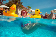 Woman with yellow duck lifebuoy. Beautiful young fat woman relaxing in the pool with yellow duck lifebuoy stock photos