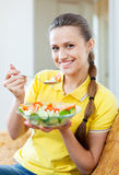 Woman in yellow eating vegetables salad stock photos