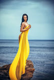 Woman in yellow fabric on the rock. Attractive woman in yellow fabric on the rock Royalty Free Stock Photography