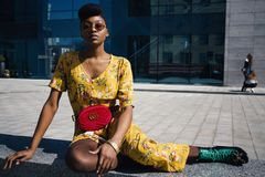 Woman in Yellow Floral Jumpsuit Sitting on Concrete Floor royalty free stock photography