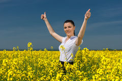 Woman in the yellow flower field show best gesture Stock Photos