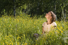 Woman in yellow flowers. Woman sitting on grass and looking up Royalty Free Stock Images