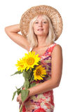 A woman with yellow flowers. A woman with yellow flowers in the hat royalty free stock photography