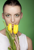 Woman with yellow flowers on green background Stock Photos