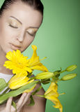 Woman with yellow flowers on green background Royalty Free Stock Image