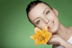 Woman with yellow flowers on green background Stock Images