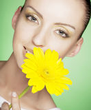Woman with yellow flowers on green background Royalty Free Stock Photography