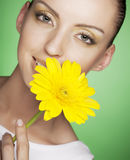 Woman with yellow flowers on green background Stock Photo