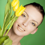 Woman with yellow flowers on green background Stock Photography