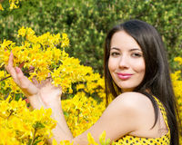 Woman with yellow flowers of rhododendron Stock Images