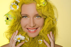 Woman with yellow hair and flowers in them. Stock Photo