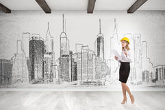 Woman in yellow hard hat and cityscape on concrete wall Stock Image
