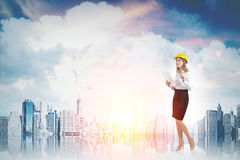 Woman in yellow hard hat and cityscape Royalty Free Stock Images