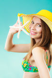 Woman in yellow hat holding white shell Royalty Free Stock Photo