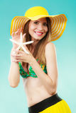 Woman in yellow hat holding white shell Royalty Free Stock Photography