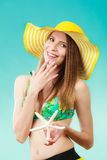 Woman in yellow hat holding white shell Stock Photography