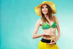 Woman in yellow hat holding white shell Royalty Free Stock Photos