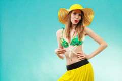 Woman in yellow hat holding white shell Royalty Free Stock Images