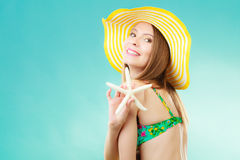 Woman in yellow hat holding white shell Stock Image