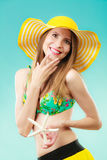 Woman in yellow hat holding white shell Royalty Free Stock Image