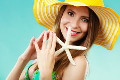 Woman in yellow hat holding white shell Stock Photos