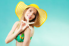 Woman in yellow hat holding white shell Stock Images