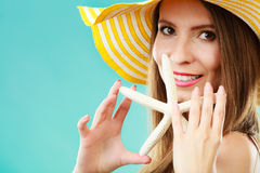 Woman in yellow hat holding white shell Stock Photo