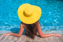 Woman in yellow hat relaxing at swimming pool Royalty Free Stock Photography