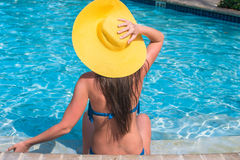 Woman in yellow hat relaxing at swimming pool Royalty Free Stock Photo
