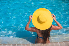 Woman in yellow hat relaxing at swimming pool Stock Images