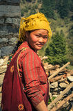 Woman with yellow headcloth in Nepal. Dolpo, Nepal - circa May 2012: Smiling native woman with long hair and with yellow headcloth wears red clothes in Dolpo Royalty Free Stock Photos