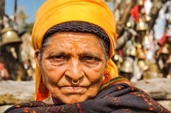 Woman with yellow headcloth in Nepal. Pathivara Devi, Nepal - circa May 2012: Old wrinkled woman with yellow headcloth and piercing in her nose wears scarf in Stock Photos