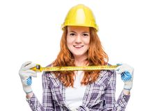 Woman in yellow helmet with tape measure in hands ready to work Stock Images