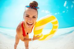 Woman with yellow inflatable lifebuoy having fun time on beach royalty free stock photos