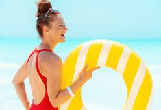 Woman with yellow inflatable lifebuoy looking into the distance stock photography
