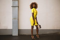 Woman in Yellow Knitted Dress Holding Beige Handbag Royalty Free Stock Photo