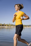 Woman in yellow at lake. A woman wearing yellow running at the lake with blue skies in the back ground Stock Photos