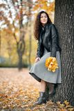 Woman with yellow leaves stand near big tree in autumn city park stock photos