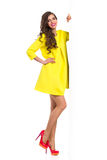 Woman In Yellow Mini Dress Posing Next To Big Banner Stock Image