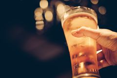Woman with yellow nail polished holding glass of cold beer with beautiful bokeh royalty free stock photography